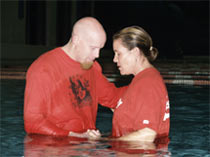 Pastor Kyle praying with a lady he is baptizing